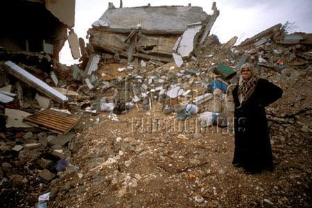 A woman stands shell-shocked in front of what used to be her home in Jenin refugee camp, Palestine. The IDF bulldozed the center of Jenin after intense fighting wth militants that left many dead.