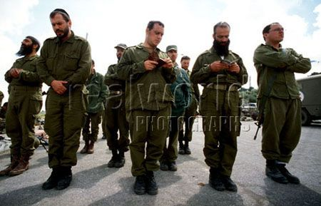 Soldiers from the Israel Defense Forces stop to pray during a break in their patrols on the outskirts of Jerusalem, Israel.