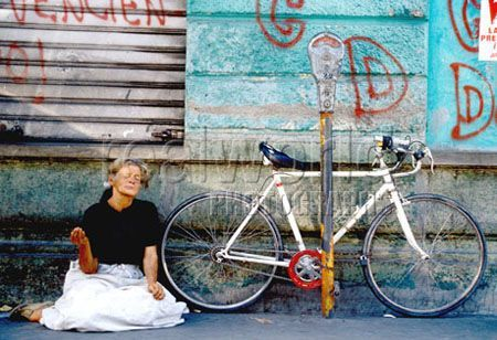 A woman begs for change next to a bicycle on the mean streets of San Salvador, El Salvador, Central America.