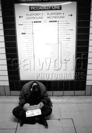 A passed out homeless man uses a home made sign hoping for change at the foot of Piccadilly underground line in London, England, UK.