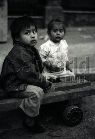 Two children give the camera a sharp look while playing in a street in downtown Guatemala City, Guatemala, Central America.